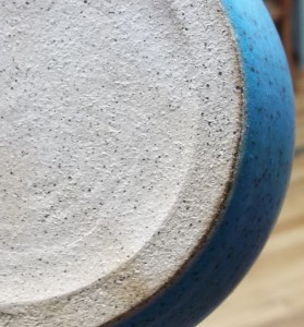 The rough, gray, speckled bottom of a stoneware bowl